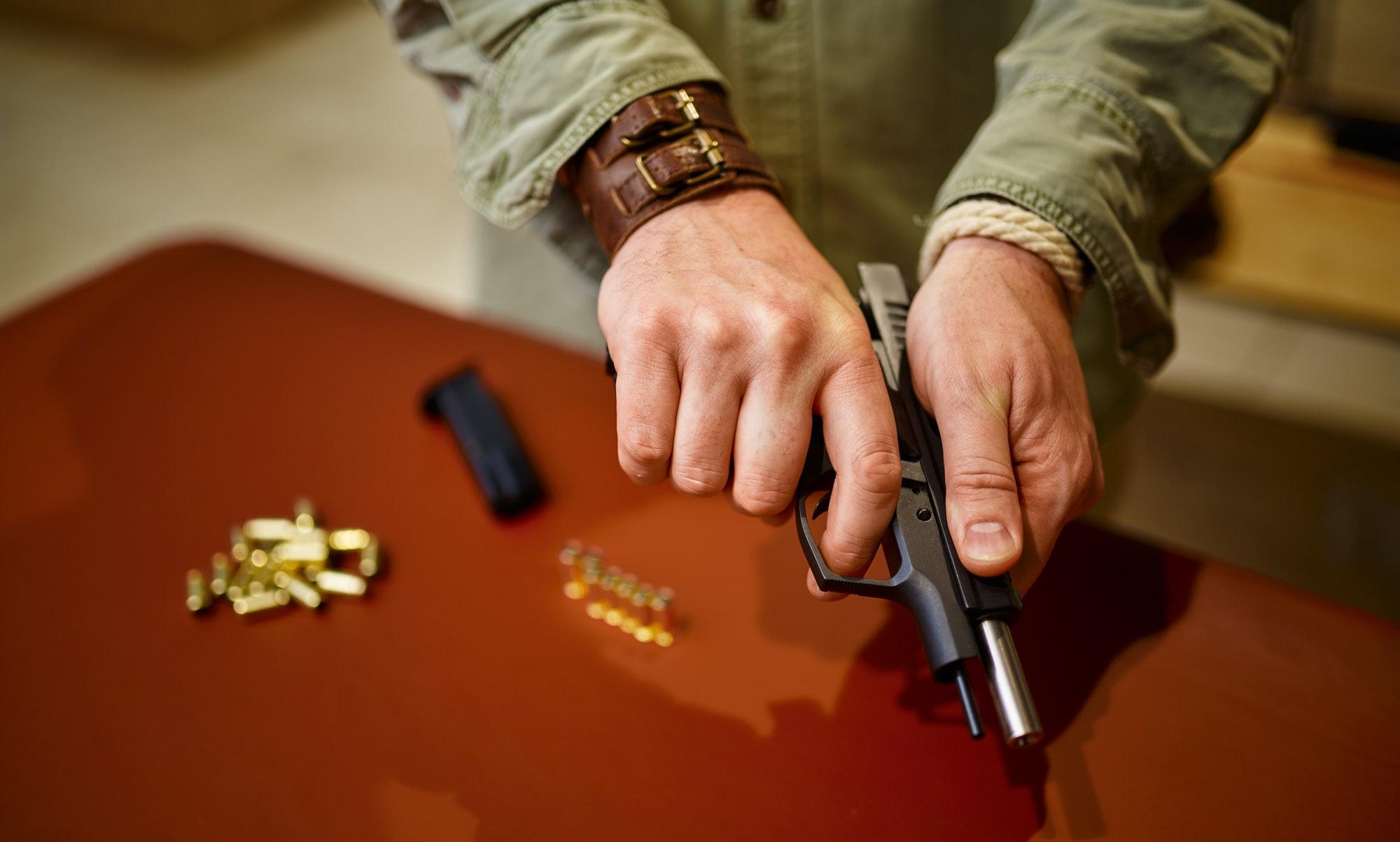 Man loads the gun with bullets in gun store